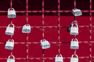Grey padlocks at red fence - symbol of security